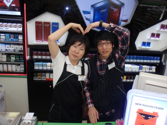 Take a picture of 2 family mart employees making a heart with their arms- 50